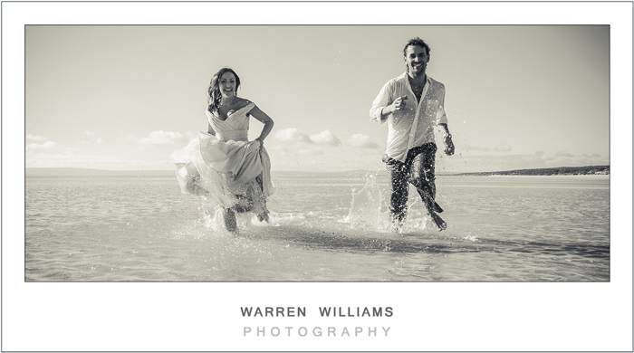 Bride and groom running through water