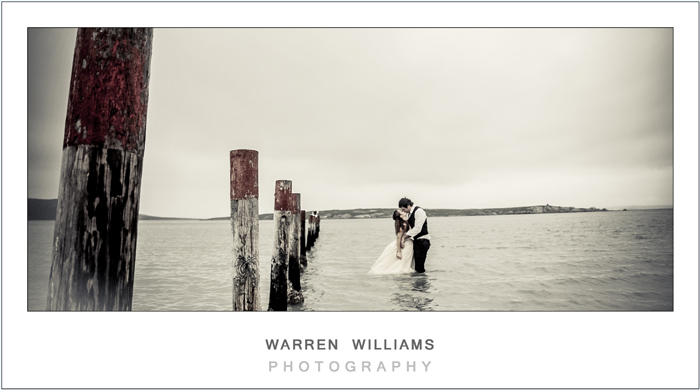Bride and groom kissing in sea water