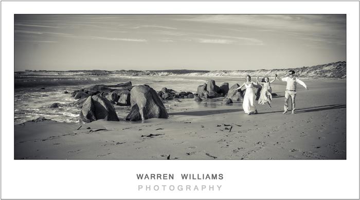 Bride, groom, flowergirl on beach