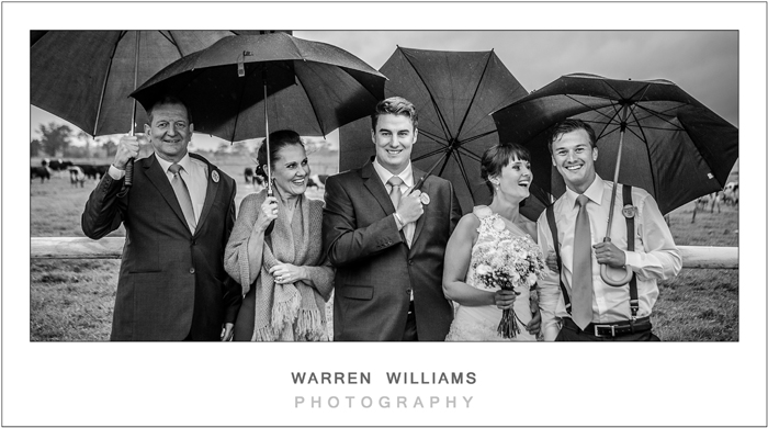 Bride and groom in rain with parents