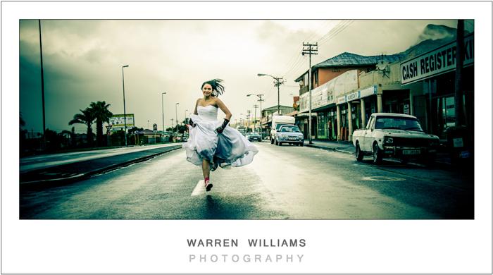 beautiful photo of bride running down road trashing her dress
