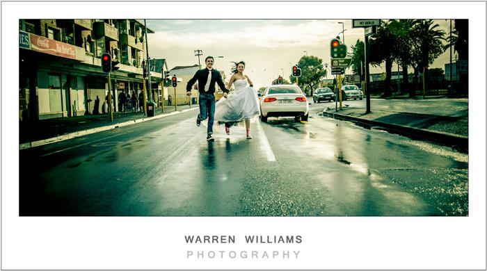 bride and groom run down urban road