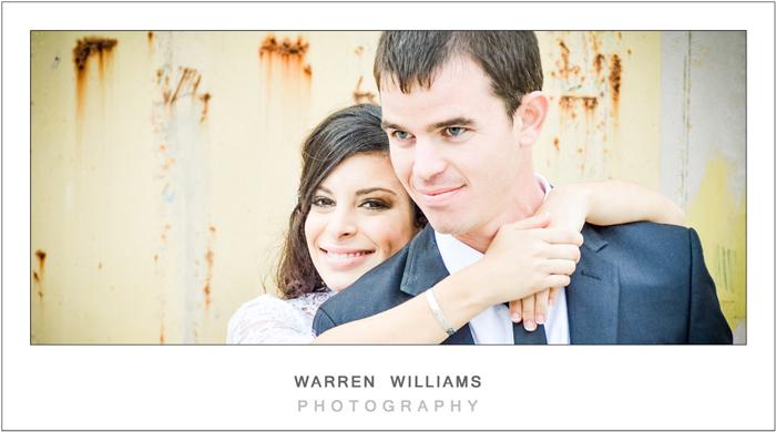 bride hugs groom against rusted wall