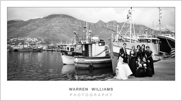 Bridal party against fishing boats